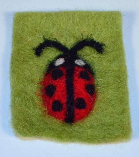 Marienkäfer auf grünem Rechteck aus Filz, von Jim Knopf